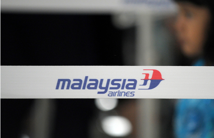 A girl walks past a Malaysian Airlines logo (MAS) at the Kuala Lumpur International Airport (KLIA) in Sepang, outside Kuala Lumpur on March 9, 2014.