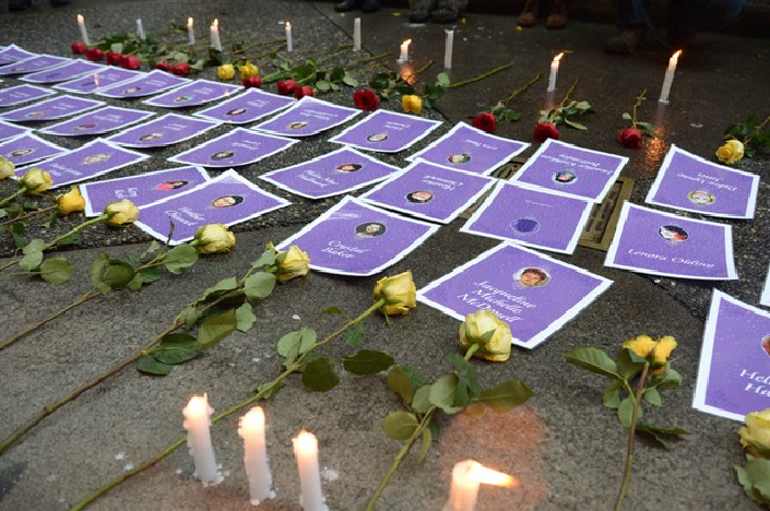 Candles and flowers are placed next to the pictures and names of those missing from the downtown eastside during a small vigil during the delivery of the report of the Missing Women Inquiry in Vancouver, Dec.17, 2012. THE CANADIAN PRESS/Jonathan Hayward.