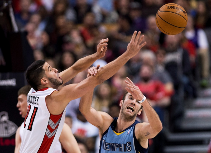 Toronto Raptors guard Greivis Vasquez, left, battlesd for the loose ball against Memphis Grizzlies guard Nick Calathes, right, during first half NBA basketball action in Toronto on Friday, March. 14, 2014. THE CANADIAN PRESS/Nathan Denette.