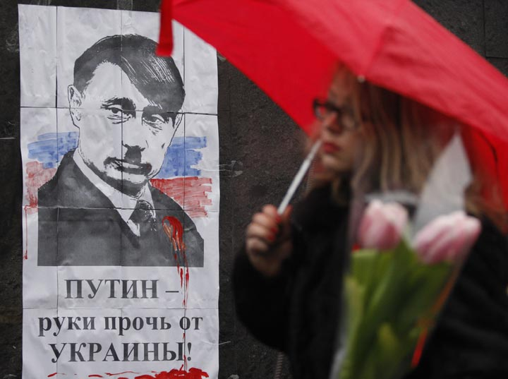 """A woman walks in front of poster depicting Russian President Vladimir Putin as Adolf Hitler and signed """"Hands off  Ukraine"""" in Kiev on March 3, 2014.  Yury Kirnichny/AFP/Getty Images."""