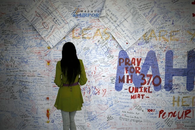 A woman reads messages and well wishes to people involved with the missing Malaysia Airlines jetliner MH370, Saturday, March 15, 2014 in Sepang, Malaysia.