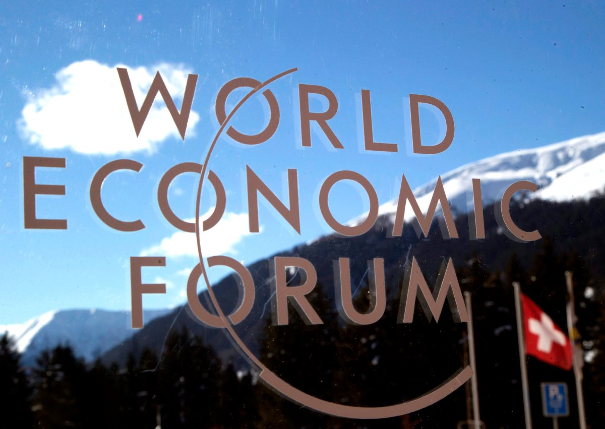 The logo of the Forum is seen through a window with the alps in the background during the World Economic Forum in Davos, Switzerland, Wednesday, Jan. 22, 2014. AP Photo/Michel Euler