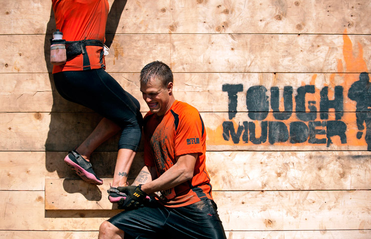 One participant helps another over the Berlin Wall obstacle at a Tuff Mudder event.