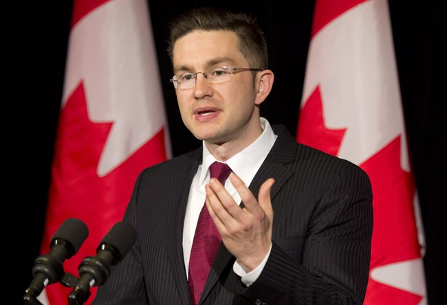 Pierre Poilievre speaks with the media about the Supreme Court decision on the Senate and the Fair Elections Act during a news conference in Ottawa on April 25, 2014.