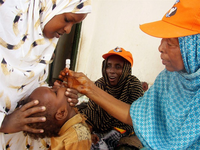 A World Health Organization official give a dose of Polio Vaccine to Somali child in Mogadishu, Somalia, Monday, Sept. 11, 2006.