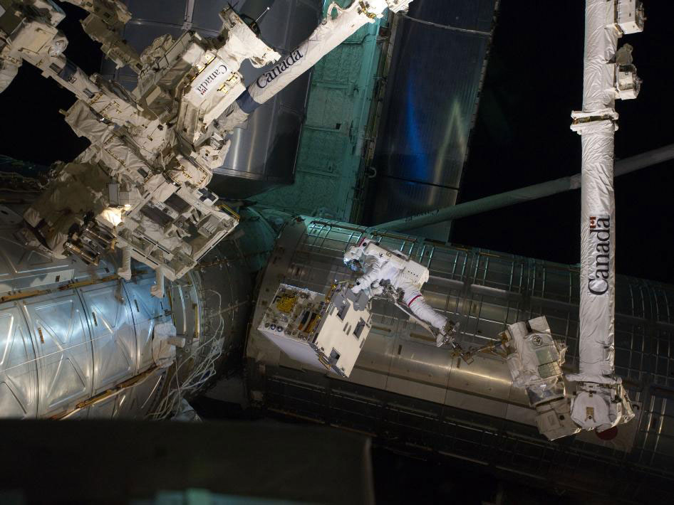Astronaut Mike Fossum works with Canadarm 2, towards Dextre on the ISS.