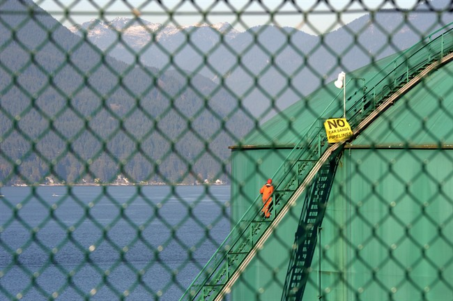 An activist walks up the stairs of an oil storage tank at the Kinder Morgan facility in Burrard Inlet, B.C. on Oct. 16, 2013. THE CANADIAN PRESS/Jonathan Hayward.