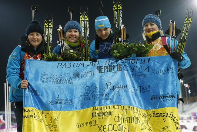 FILE - In this Friday, Feb. 21, 2014, file photo Ukraine's relay team Vita Semerenko, Juliya Dzhyma, Olena Pidhrushna and Valj Semerenko, from left, celebrate with a Ukrainian flag with writings on it after winning the gold during the women's biathlon 4x6k relay, at the 2014 Winter Olympics in Krasnaya Polyana, Russia.
