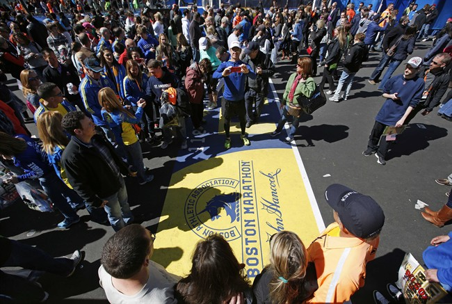 A large crowd gathers to pose for photos at the Boston Marathon finish line, one day before the race, Sunday, April 20, 2014, in Boston.