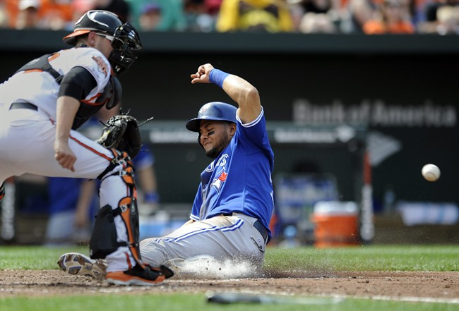 Toronto Blue Jays' Melky Cabrera, right, slides safely across home plate on a single hit by Colby Rasmus as Baltimore Orioles catcher Matt Wieters awaits the throw in the sixth inning of a baseball game on Sunday, April 13, 2014, in Baltimore. (AP Photo/Gail Burton).