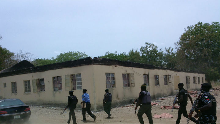 Security walk past burned government secondary school Chibok, where gunmen abducted more than 200 students on Apr. 14.