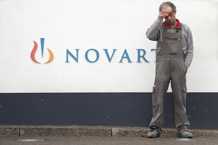A man smokes a cigarette by the logo of Novartis in Basel on October 25, 2011.