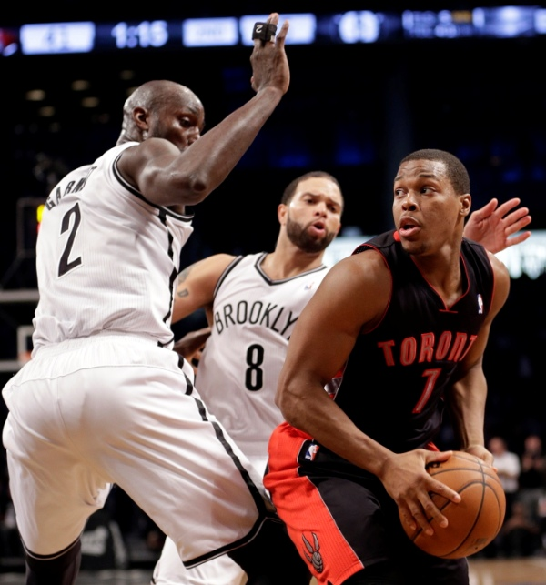 Toronto Raptors' Kyle Lowry (7) looks to pass away from Brooklyn Nets' Kevin Garnett (2) and Deron Williams (8) during the first half of Game 3 of an NBA basketball first-round playoff series Friday, April 25, 2014, in New York. (AP Photo/Frank Franklin II).
