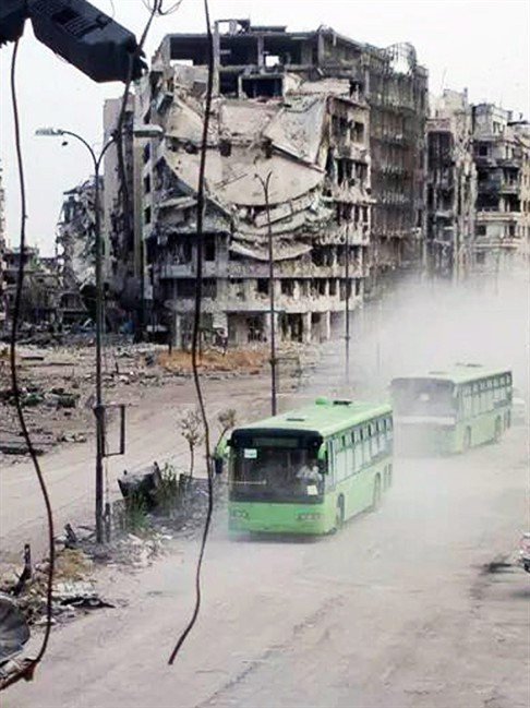 This Wednesday, May 7, 2014 photo provided by the anti-government activist group Coordination Committee of Khalidiya Neighborhood in Homs, which has been authenticated based on its contents and other AP reporting, shows buses carrying Free Syrian Army fighters leaving Homs, Syria. Exhausted and worn out from a year-long siege, hundreds of Syrian rebels on Wednesday left their last remaining bastions in the heart of the central city of Homs under a cease-fire deal with government forces.