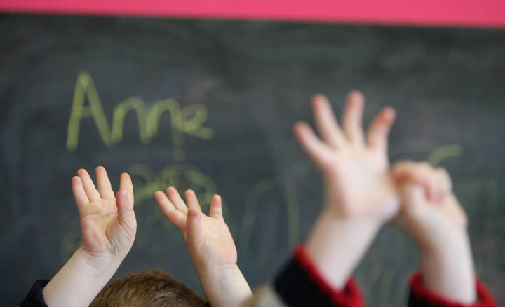 FILE: Children raise their hands in a school classroom.