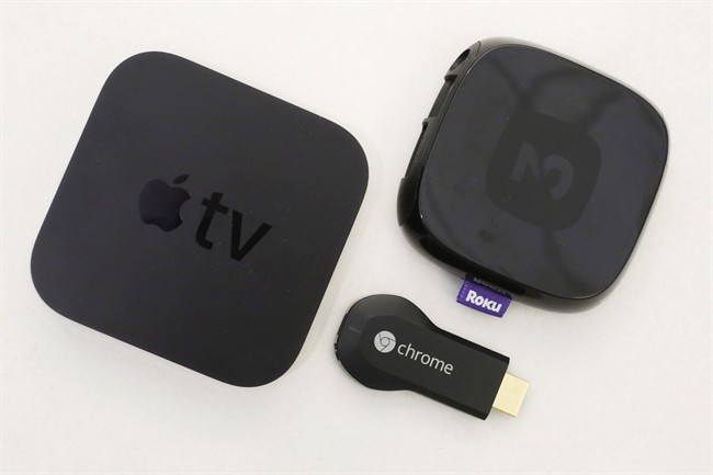 An Apple TV device, left, is shown alongside Google's Chromecast, center, and the Roku 2.