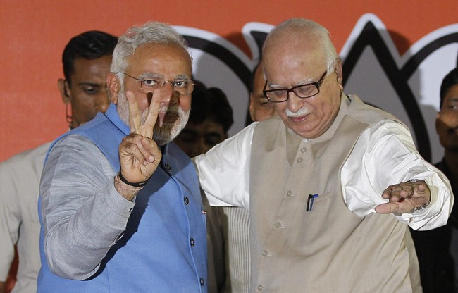 Opposition Bharatiya Janata Party (BJP) leader and India's next prime minister Narendra Modi, left, flashes the victory symbol standing next to senior party leader L.K. Advani at the party headquarters in New Delhi, India, Saturday, May 17, 2014.