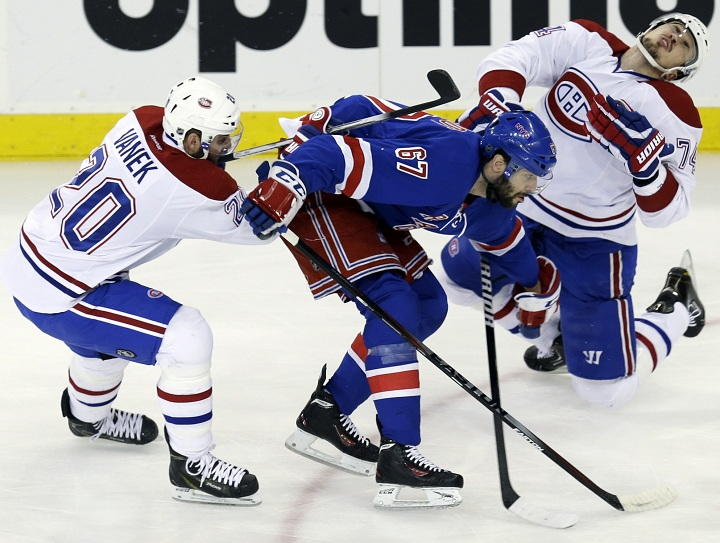 New York Rangers' Benoit Pouliot, center, commits a high sticking penalty against Montreal Canadiens' Alexei Emelin, right, while Thomas Vanek chases the puck during the first period of Game 4 of the NHL hockey Stanley Cup playoffs Eastern Conference finals, Sunday, May 25, 2014, in New York.