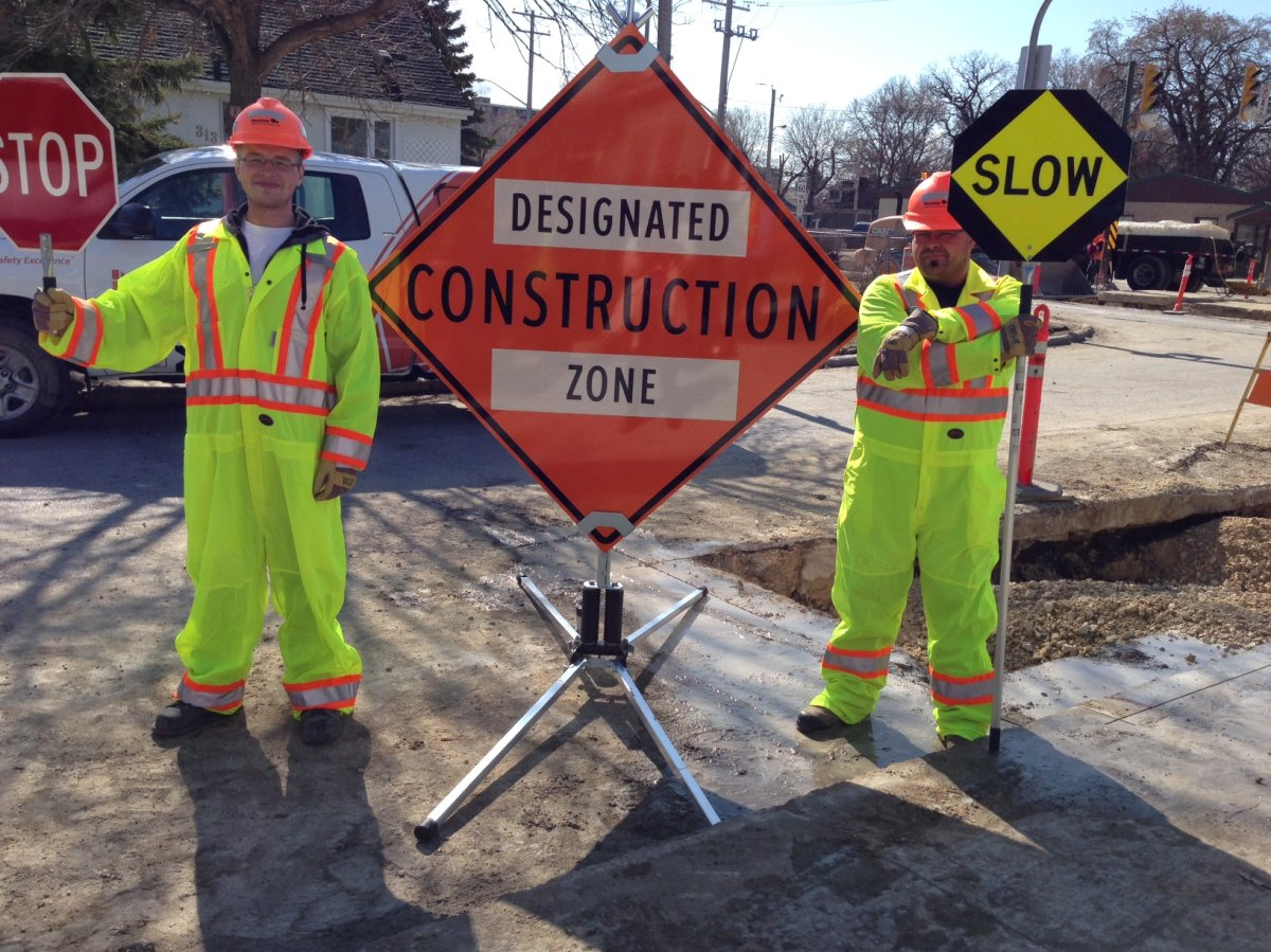 Construction workers display new road signs .