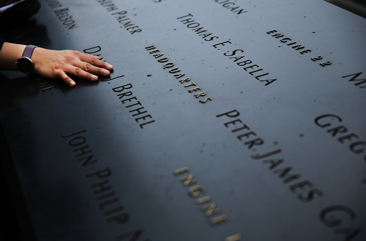 A woman places a hand on the names engraved along the South reflecting pool at the Ground Zero memorial site during the dedication ceremony of the National September 11 Memorial Museum in New York May 15, 2014 in New York City.