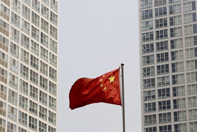 A Chinese national flag flutters in the wind in between a high-rise residential and office complex in Beijing, China Monday, May 19, 2014.