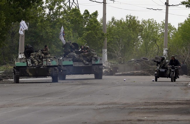 Pro-Russian gunmen atop armoured personal carriers passing by barricades on a road leading into Slovyansk, eastern Ukraine, Monday, May 5, 2014.