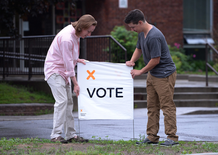 Election workers prepare to open a poll in Carleton Place, Ont. on Thursday June 12, 2014.