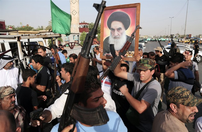 Iraqi Shiite tribal fighters raise their weapons and chant slogans against the al-Qaida-inspired Islamic State of Iraq and the Levant, after authorities urged Iraqis to help battle insurgents, in Baghdad's Sadr City, Iraq, Wednesday, June 18, 2014.