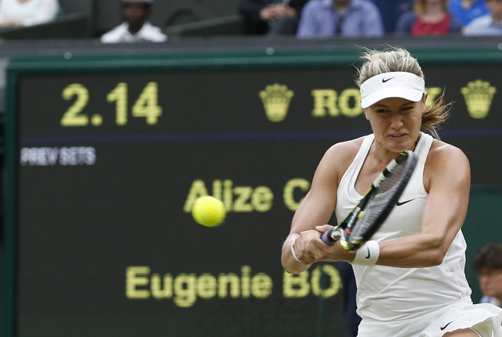 Eugenie Bouchard plays a return to Alize Cornet of France during their women's singles match at the All England Lawn Tennis Championships in Wimbledon, London, Monday, June 30, 2014.