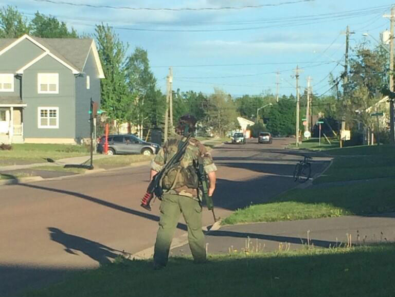 Two guns are seen on the back of an armed man, believed to be Justin Bourque, in Moncton, N.B., on June 4.