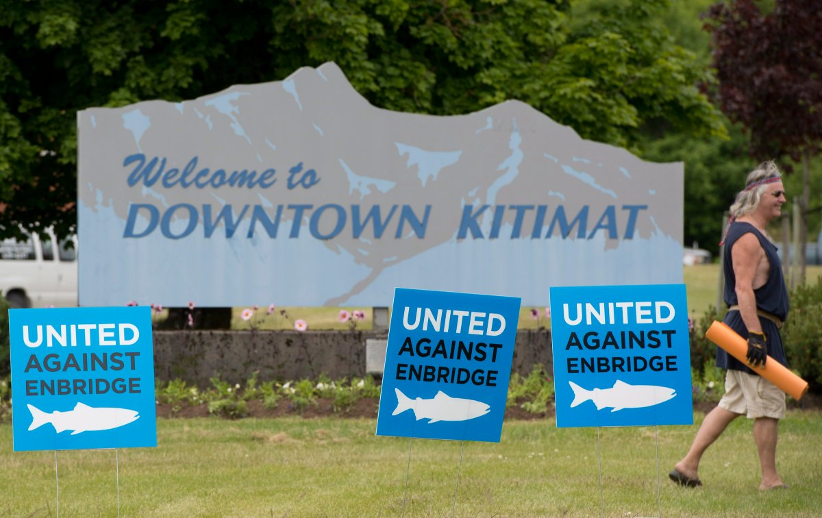 A man walks by signs opposing the Enbridge pipeline in downtown Kitimat, B.C. Tuesday, June, 17, 2014.