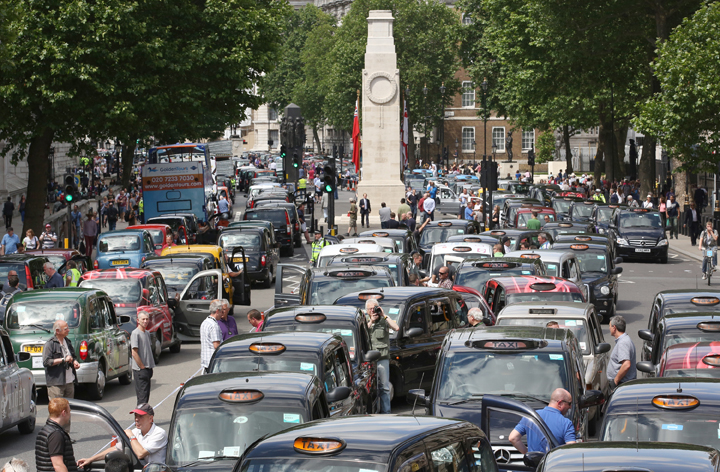 Taxis blockade Whitehall on June 11, 2014 in London, England. London's licensed black taxi drivers are campaigning against the introduction of the 'Uber' taxi smartphone app in the United kingdom.