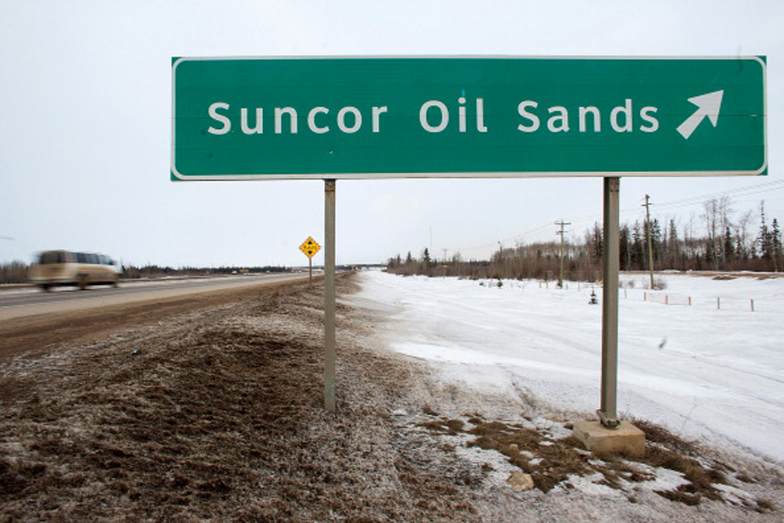 A sign directing traffic to the Suncor Energy Inc. base plant stands at the Athabasca Oil Sands near Fort McMurray, Alberta, Canada, on Tuesday, March 26, 2013. Canadian light oil prices retreated from a six-month high on the spot market reached last week as production slipped and refineries prepared for maintenance. Photographer: Brett Gundlock/Bloomberg via Getty Images