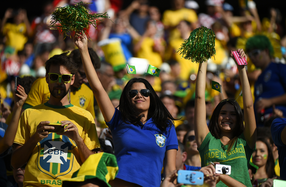 Brazilian fans cheer prior to the Group A football match between Brazil and Croatia at the Corinthians Arena in Sao Paulo during the 2014 FIFA World Cup on June 12, 2014. AFP PHOTO / FABRICE COFFRINI (Photo credit should read FABRICE COFFRINI/AFP/Getty Images)
