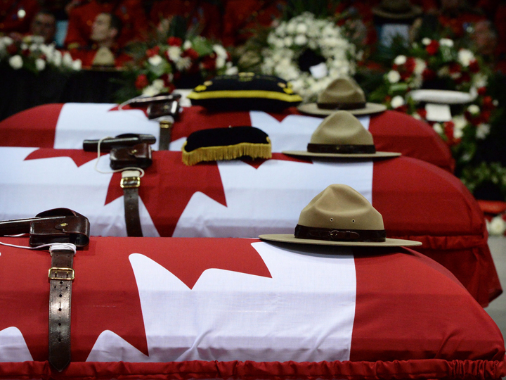 Stetsons rest on the caskets of the three slain RCMP officers, Const Dave Ross, Const. Douglas Larche and Const. Fabrice Gevaudan at a regimental funeral in Moncton, N.B., Tuesday, June 10, 2014.