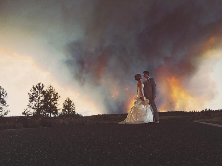 In this Saturday, June 7, 2014 photo provided by Josh Newton, newlyweds Michael Wolber and April Hartley pose for a picture near Bend, Ore., as a wildfire burns in the background. Their ceremony had to be evacuated and their reception was relocated because of the fire.