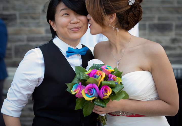 Jen Chang, left, and Inae Lee pose for photos before joining over 100 gay couples in a mass wedding during World Pride 2014 at Casa Loma in Toronto, on Thursday, June 26, 2014.