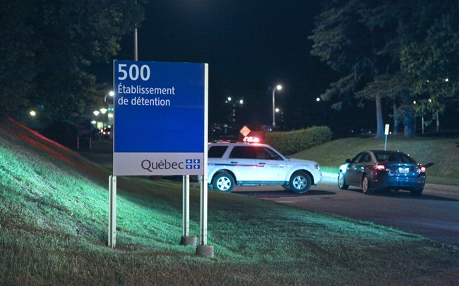 Police cars are shown in front of the Orsainville Detention Centre near Quebec City on Saturday June 7, 2014. There has been another jailbreak in Quebec involving a helicopter. Quebec Provincial Police say three inmates have escaped from the Orsainville Detention Centre.