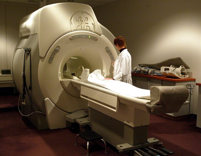 A technician operates an MRI machine at a private clinic in Calgary on Jan. 12, 2005. Saskatchewan doctors oppose a plan that will allow people to pay privately for MRIs.