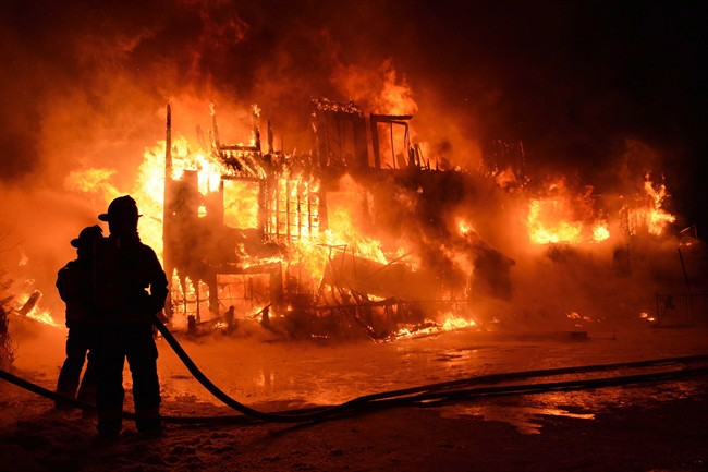 Fire engulfs a seniors residence in L'Isle-Verte, Que., early Thursday, Jan.23, 2014. A multimillion-dollar lawsuit has been filed against the Quebec town where 32 people died in a fire at a seniors' home last January.