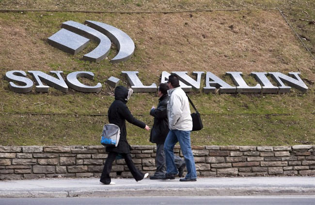 Pedestrians walk past the offices of SNC-Lavalin in Montreal.