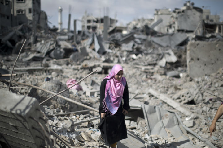Palestinian woman walks across the rubble of destroyed buildings and homes in the Shejaiya residential district of Gaza City on July 26, 2014.