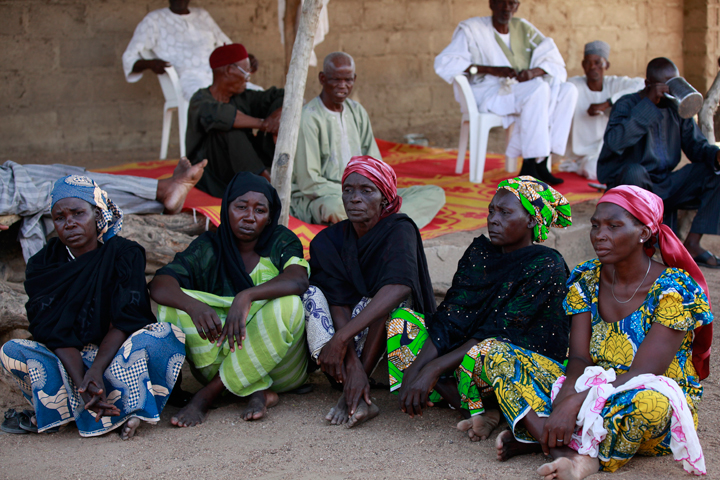 FILE- In this Sunday, May 18, 2014 file photo some of the parents of the kidnapped school girls sit outside a compound during a meeting in Chibok, Nigeria. At least 11 parents of the more than 200 kidnapped Nigerian schoolgirls will never see their daughters again. Since the mass abduction of the schoolgirls by Islamic extremists three months ago, at least 11 of their parents have died and their hometown, Chibok, is under siege from the militants, residents report.