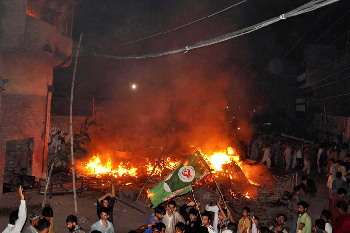This photograph taken on July 27, 2014 shows an angry mob after they set fire to household items belonging to a minority Ahmadi Muslim resident in the low-income Arafat Colony of the eastern city of Gujranwala, some 112 kilometres north of Lahore. An angry mob in Pakistan torched an Ahmadi Muslim minority neighbourhood killing a woman and two girls in a row over blasphemy, police said, in the latest attack on one of the country's most persecuted groups.