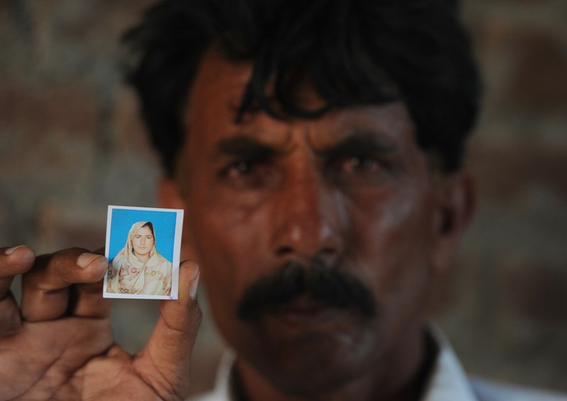 Pakistani resident Mohammad Iqbal poses for a photograph as he holds up an image of his wife Farzana Parveen, who was beaten to death with bricks by her father and other family members for marrying a man of her own choice, in Chak 367 some 40 kms from Faisalabad on May 30, 2014. AFP PHOTO/Aamir QURESHI.
