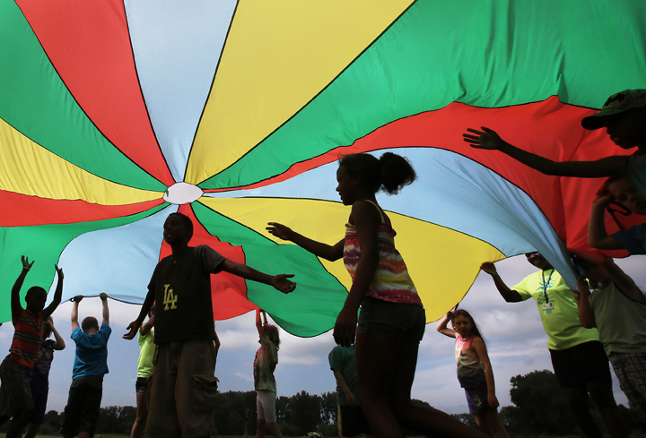 FILE PHOTO: Elementary school students enrolled in a summer camp program play under a colorful canopy.