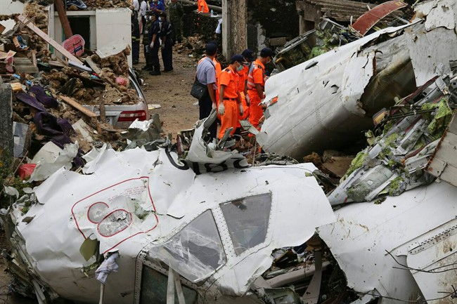 Rescue workers survey the wreckage of TransAsia Airways Flight GE222 on the Taiwanese island of Penghu Thursday, July 24, 2014. The plane attempting to land in stormy weather crashed on the island late Wednesday, killing more than 40 people and wrecking houses and cars on the ground.