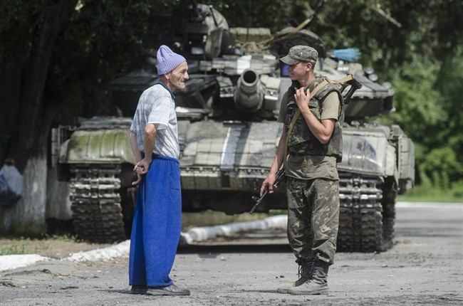 A local citizen speaks to a Ukrainian government soldier guarding a checkpoint outside the city of Siversk, Donetsk region, eastern Ukraine, Saturday, July 12, 2014.
