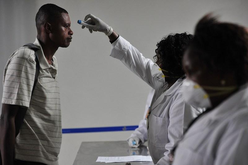 Kenyan health officials take passengers temperature as they arrive at the Jommo Kenyatta International Airport (JKIA) on August 14, 2014 in Nairobi. AFP PHOTO / SIMON MAINA .