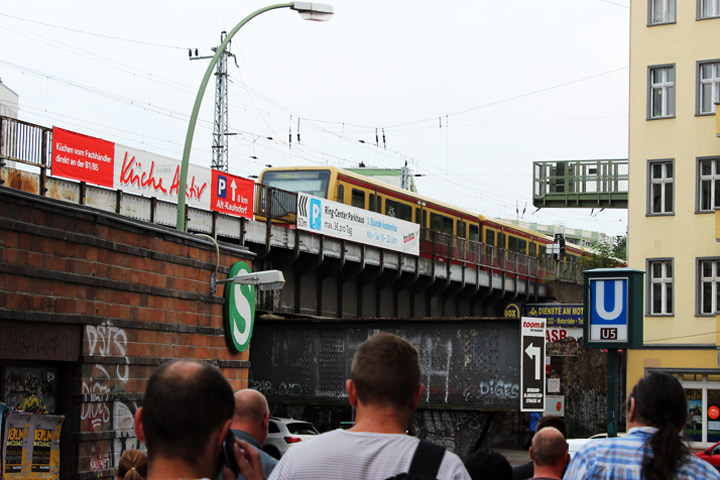 An elevated S-Bahn train glides above a busy street in East Berlin.
